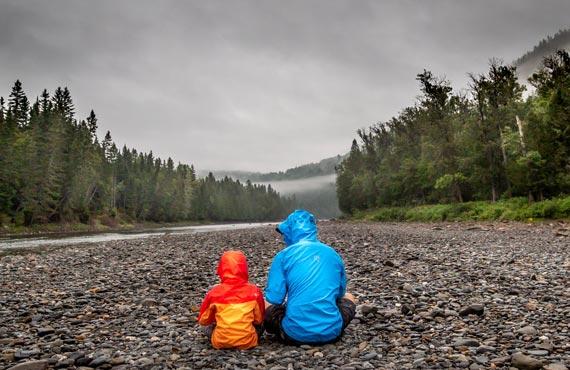 Parent et enfant près d'une rivière entourée de forêts de sapins